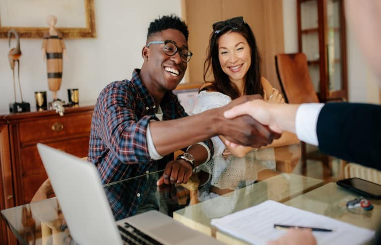 Young real estate agent shaking hands with new real estate prospects
