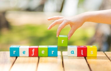 """A hand using letter blocks to spell out the word """"referrals"""""""