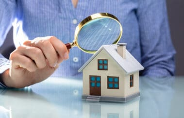 Close-up Of A Businesswoman's Hand Holding Magnifying Glass Over House Model Over Desk