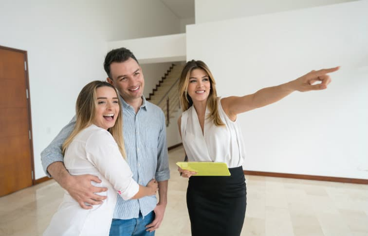Real estate agent showing a property to a young couple