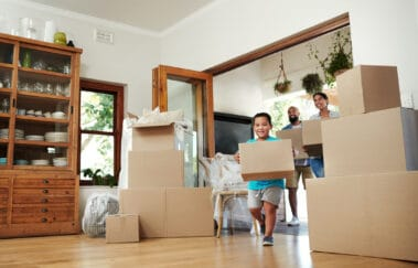 Shot of young family of three carrying moving boxes into their new home