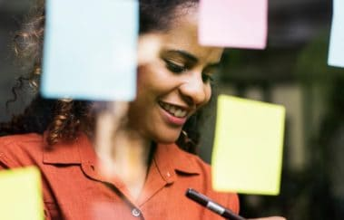 women with post-it notes on glass