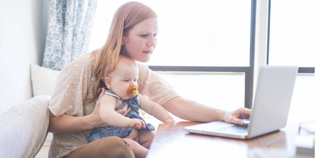 real estate mom works on continuing education with baby in lap