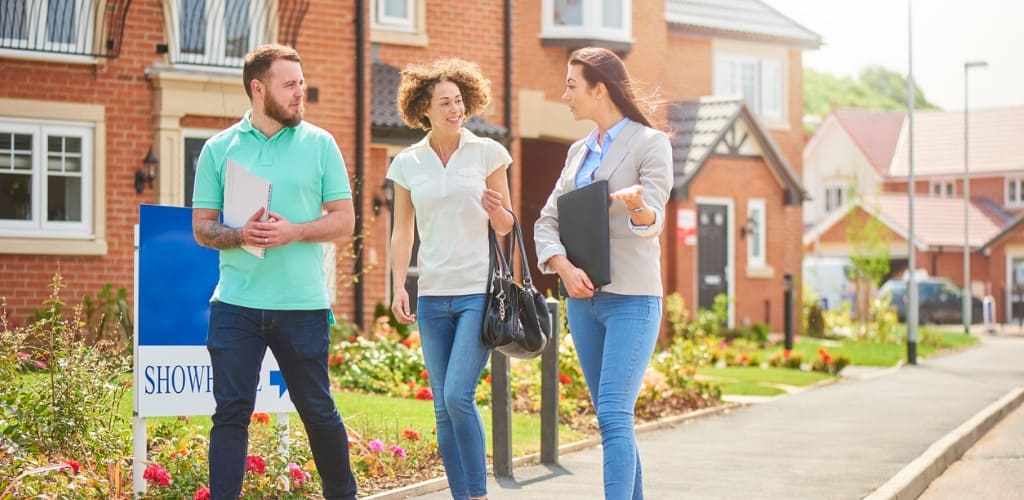 first-time homebuyers looks at housing with real estate agent