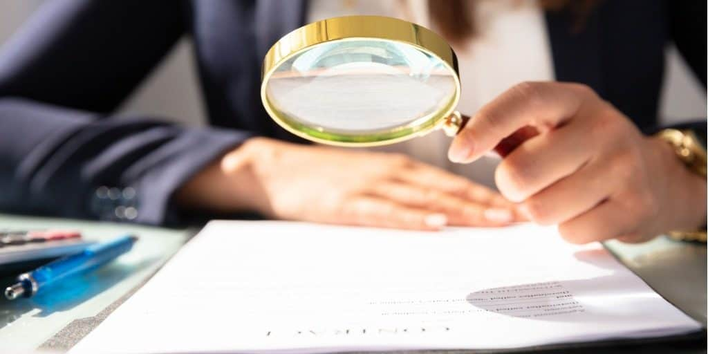 business woman looking at contract through magnifying glass