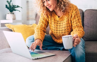 Real estate agent wearing warm sweater and working on her laptop, following our tips for real estate agents to stay busy this winter
