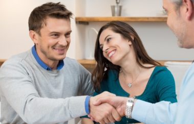 young couple shakes hands with real estate agent