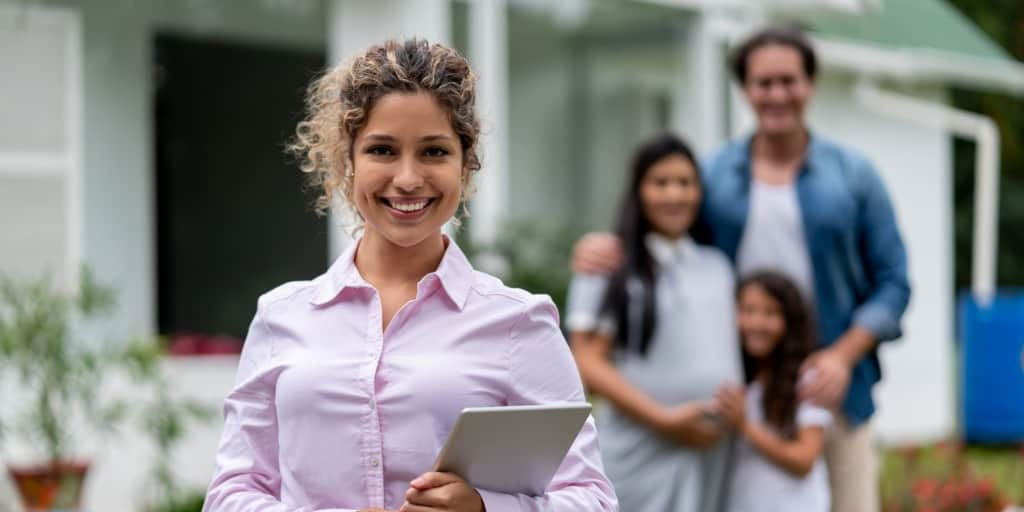 real estate agent holding clipboard in front of sold house