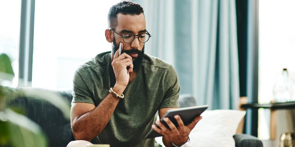 man looking at bank account on tablet