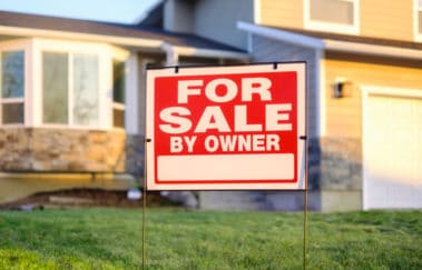 For Sale By Owner sign on the front lawn of a single-family home