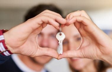 Portrait of a happy young couple proudly displaying the keys to their new house