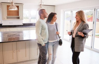 Successful real estate agent showing a modern house to a young couple