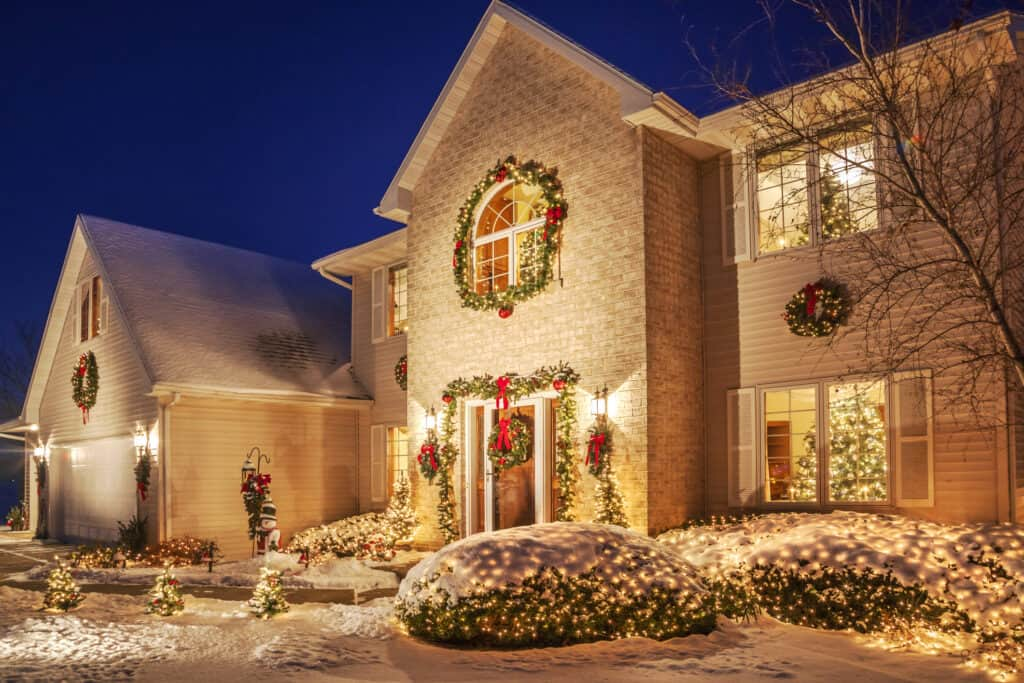 Holiday decorated home at evening with Christmas lighting, fluffy snow