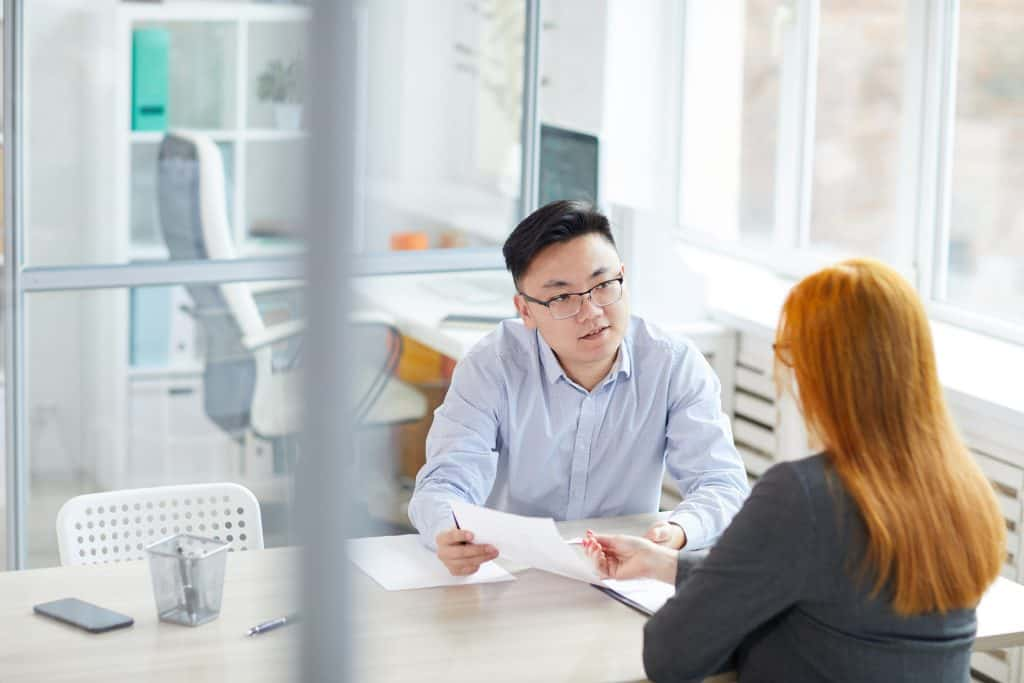 Portrait of young Asian businessman interviewing young woman for job position in modern office, copy space