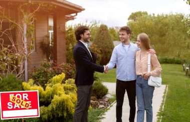 Millennial couple shaking hands with real estate agent near their new house outdoors, copy space