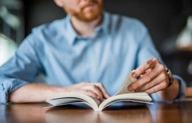 Young man reading a book hand close up.