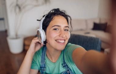 Selfie of a young woman listening to the music and enjoying at home.