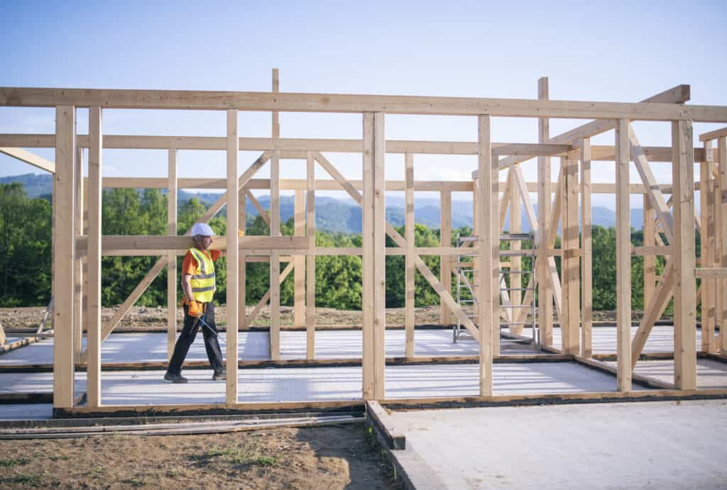 Builder walking with wooden beam on shoulder in an unfinished wooden construction site.