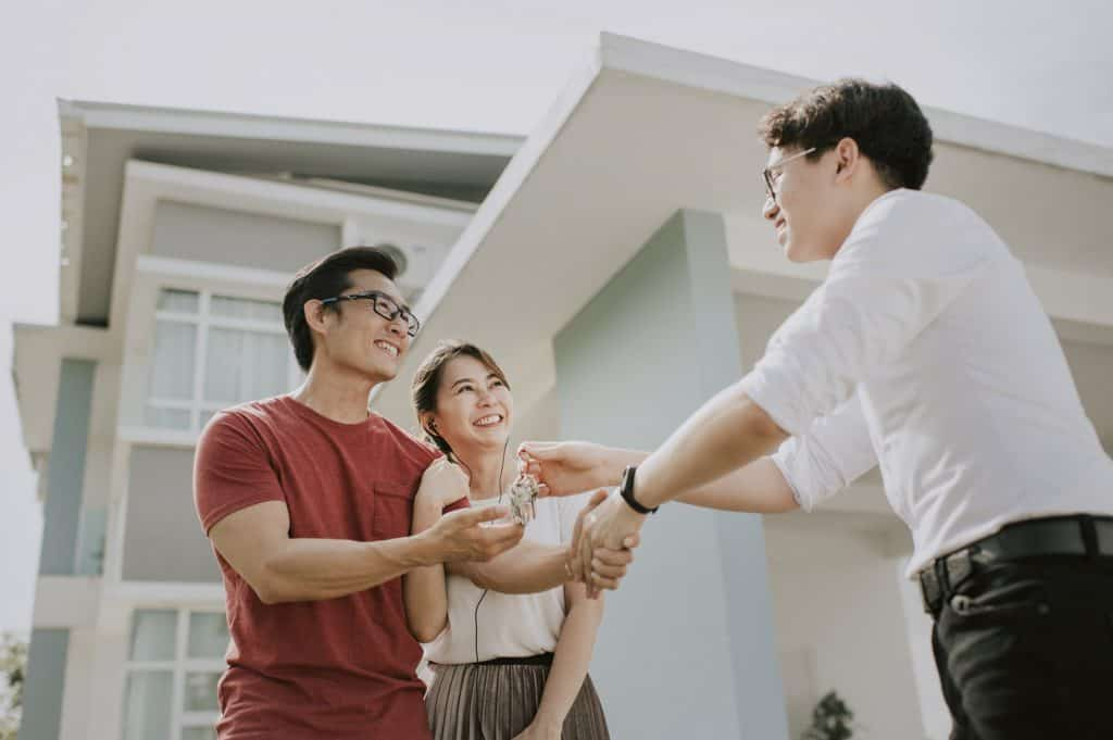real estate agent giving keys to house to couple