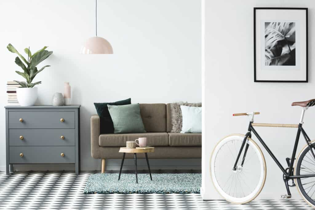 Bicycle and poster in cozy living room interior with wooden table near brown couch and grey cabinet