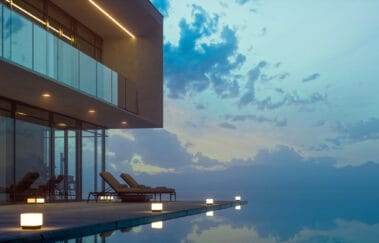 Luxurious villa with private infinity pool and chaise lounges at summer in dusk.